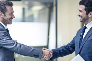 Two business men shaking hands after talking about the agreement.